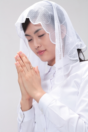 Close up shot of A female Asian wearing a mass veil praying with eyes closed