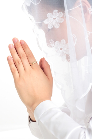 Close up shot of Side shot of A female Asian wearing a mess veil praying with a rosary ring