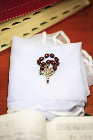 Close up shot of a brown rosary laid on the folded white mass veil
