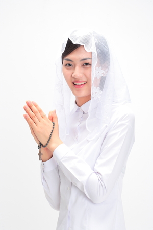 A female Asian wearing a mass veil praying with toothy smile as holding a rosary in hand Stock Photo