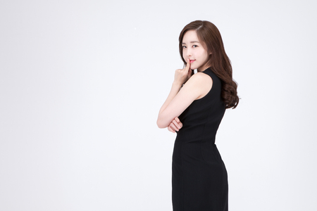 Young beautiful Asian woman in black mini dress posing in the studio - isolated on white Stok Fotoğraf