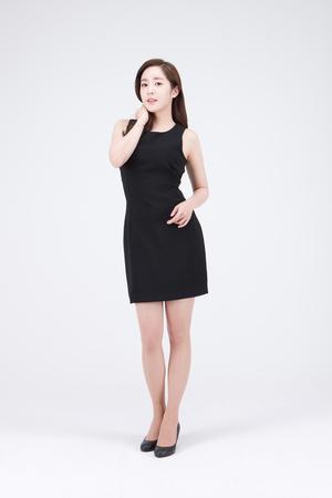 Jonge mooie Aziatische vrouw in het zwarte minikleding stellen in de studio - die op wit wordt geïsoleerd