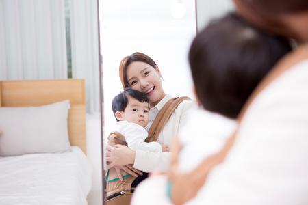部屋で鏡を見て赤ちゃんと一緒に働くママ
