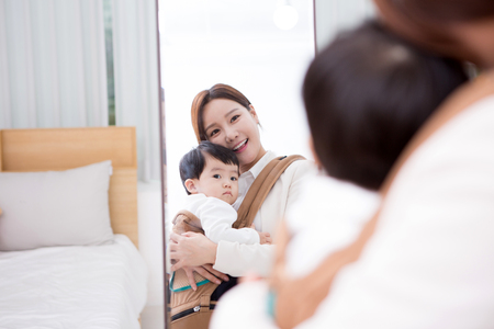 Working mom with the baby looking at the mirror in the room Foto de archivo