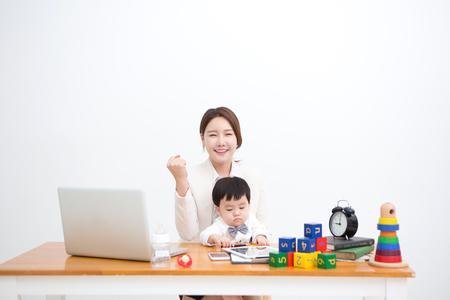 おもちゃ - 白で隔離で机の上に座っている赤ちゃんと一緒に働くママ