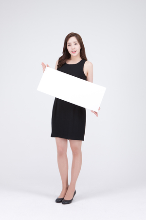 republic of korea: Young beautiful Asian woman in black mini dress holding a blank board - isolated on white