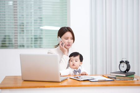 Working mom with the baby answering the phone at work