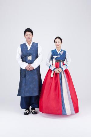 Jong Aziatisch paar in Hanbok, Koreaanse traditionele kleren, die in de studio stellen - die op wit wordt geïsoleerd