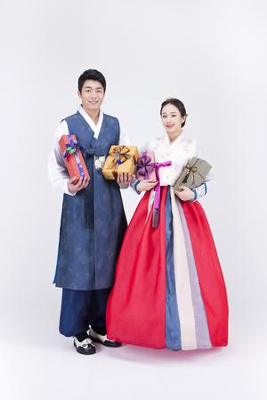 Jong Aziatisch paar in Hanbok, Koreaanse traditionele kleding, poseren met cadeau dozen - geïsoleerd op wit Stockfoto