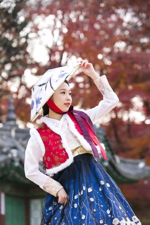 Young Asian woman in Hanbok, Korean traditional clothes posing in Hanok, Korean traditional house Banco de Imagens