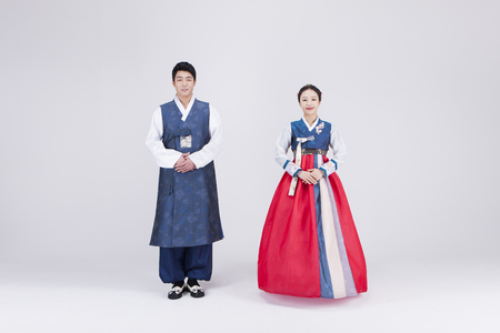 Young Asian couple in Hanbok, Korean traditional clothes, posing in the studio - isolated on white
