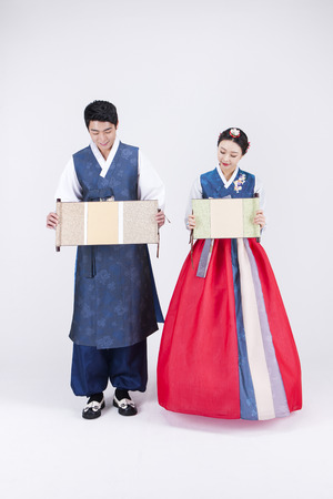 hanbok: Young Asian couple in Hanbok, Korean traditional clothes, holding an oriental blank scroll banners - isolated on white