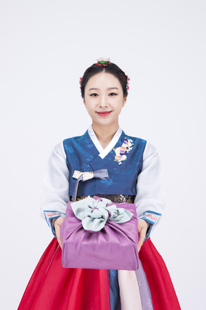 Young Asian woman in Hanbok, Korean traditional clothes, posing with a gift - isolated on white