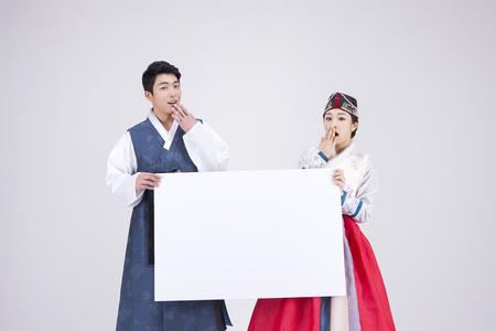Jong Aziatisch paar in Hanbok, Koreaanse traditionele kleren, die een lege raad houden - die op wit wordt geïsoleerd