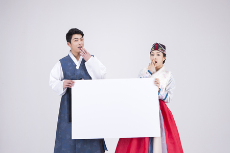 Young Asian couple in Hanbok, Korean traditional clothes, holding a blank board - isolated on white