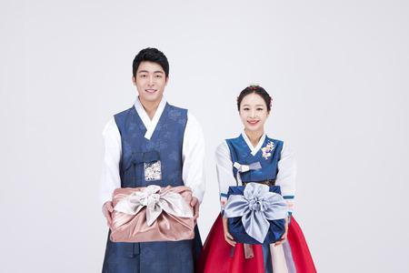 Jong Aziatisch paar in Hanbok, Koreaanse traditionele kleding, poseren met cadeau dozen - geïsoleerd op wit Stockfoto - 83914356