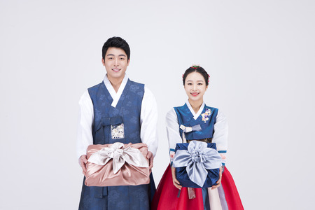 Young Asian couple in Hanbok, Korean traditional clothes, posing with gift boxes - isolated on white