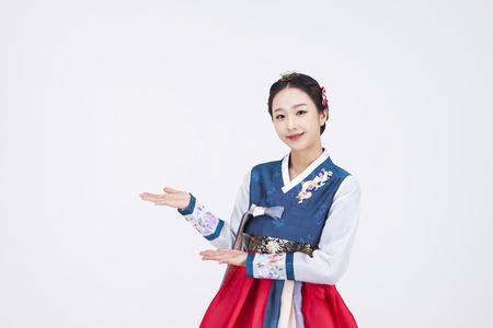 Jonge Aziatische vrouw in Hanbok, Koreaanse traditionele kleren, die in de studio stellen - die op wit wordt geïsoleerd