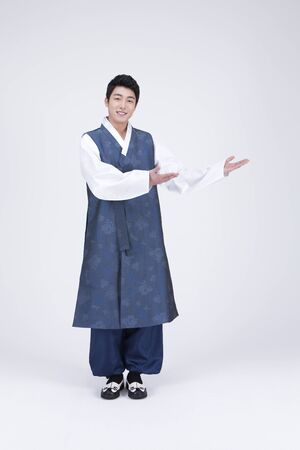 Young Asian man in Hanbok, Korean traditional clothes, posing in the studio - isolated on white