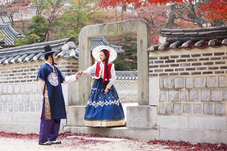 한복의 젊은 아시아 신혼 부부, 한옥 주변 산책 한국 전통 의상