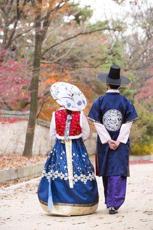 Jong Aziatisch jonggehuwdepaar in Hanbok, Koreaanse traditionele kleren die rond Hanok, Koreaans traditioneel huis lopen