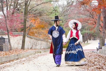 Jong Aziatisch jonggehuwdepaar in Hanbok, Koreaanse traditionele kleren die rond Hanok, Koreaans traditioneel huis lopen Stockfoto