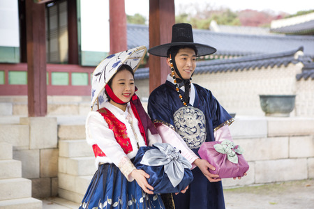 Young Asian newlywed couple in Hanbok, Korean traditional clothes posing with gifts Hanok, Korean traditional house