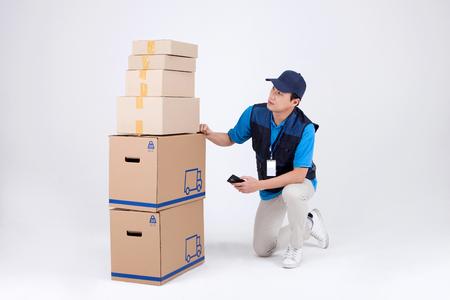 Hombre de entrega asiática con uniforme aislado en blanco - arrodillado con cajas de envíos Foto de archivo - 84466259