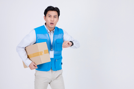 Asian delivery man wearing uniform isolated in white - looking at wrist watch with a box shipment