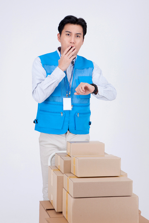 Asian delivery man wearing uniform isolated in white - posing with a stacked boxes of shipments on cart