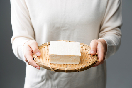 Slow food - Isolated shot of hands holding a block of tofu Stock Photo