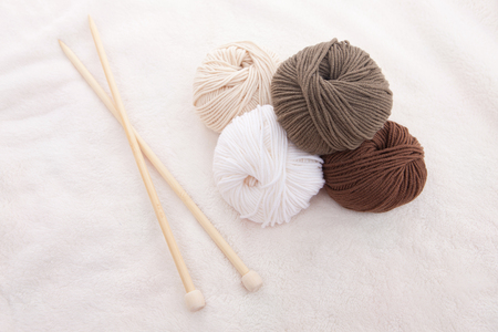 Knitting wool balls and wooden needles in white background Stock Photo