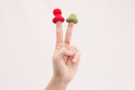 teeny: Fingers wearing teeny tiny wool hats in white background