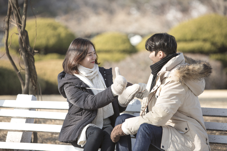 Asian couple dating at park - sitting on bench as facing each other at park