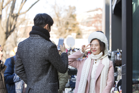 Asian couple dating in street - trying on a big fur hat