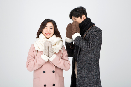 Asian couple isolated in white studio - wearing winter wool coats and gloves