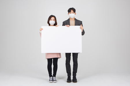Asian couple isolated in white studio - holding a big white empty board as wearing winter coats