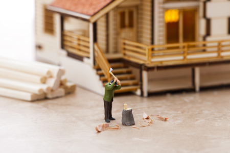 Creative miniature life - Man splitting timberlog with axe Stock Photo