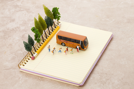 Creative miniature life - Kidsstudentstravelers getting onto a bus Stock Photo