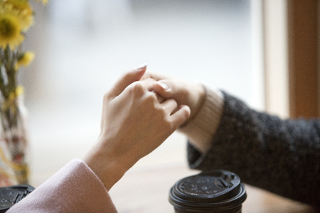 A couple holding hands across the table isolated