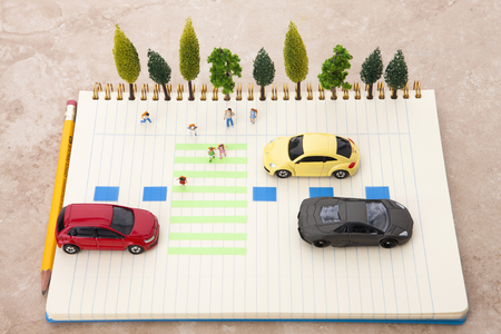 Creative miniature life - Kids crossing the crosswalk and cars at the stop lines