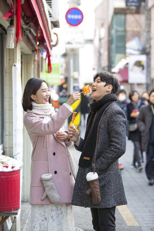 Asian couple dating in street - trying street food