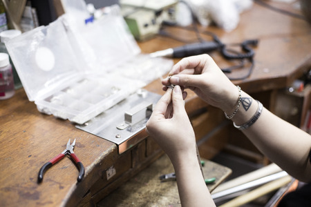jewerly: Isolated shot of bear hands of handmade craft jewerly experts making a piece Stock Photo
