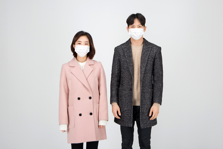 Asian couple isolated in white studio - posing as wearing winter wool coats Stock Photo