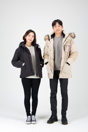 Asian couple isolated in white studio - posing as wearing winter padded coats
