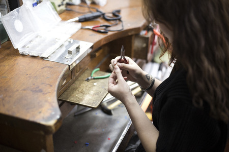 Isolated shot of hands of handmade craft jewerly experts making a piece withusing toolsmachines