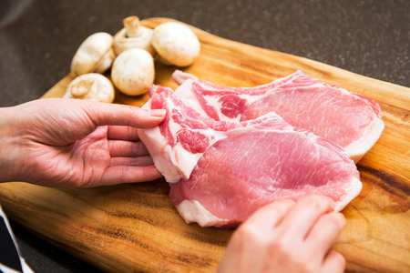 Isolated shot of cooks hands prepparing fresh ingredients - Pork Stock Photo