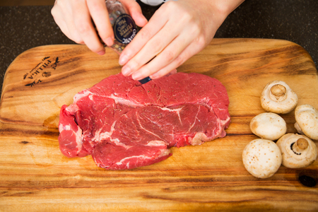 Isolated shot of cooks hands prepparing fresh ingredients - BeefSteak Stock Photo