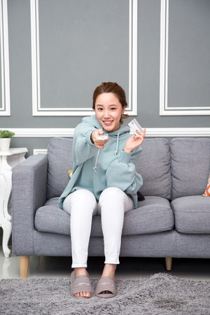 Young female Asian in pajamas watching TV in the living room/Tvroom Zdjęcie Seryjne - 84486157