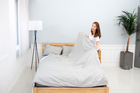 Young female Asian making bed Stock Photo
